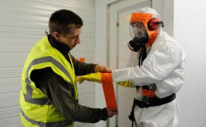 Un opérateur de désamiantage se fait aider par un collègue pour régler son équipement de protection individuelle (EPI).