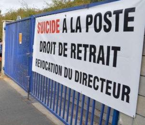 Une affiche placardées sur des grilles indique : « Suicides à La Poste. Droit de retrait. Révocation du directeur.