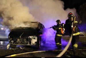 Des sapeurs-pompiers éteignent une voiture brûlée.