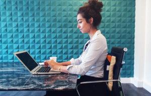 Une employée est assise dos contre le dosseret ergonomique