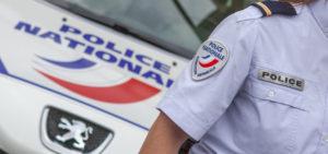 Un policier se tient devant une voiture.