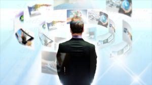 Un homme de dos se tient devant des vignettes représentant des cyber-tâches à accomplir.