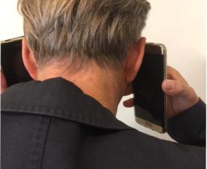 Un manager stressé tient un téléphone à chaque oreille.