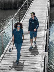 Deux jeunes personnes traversent un pont, arborant la collection C26 aux couleurs bleu pétrole du fabricant Uvex.