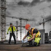 Deux opérateurs portent des gilets haute visibilité auto-éclairants sur un chantier.