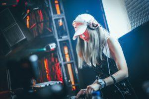 Jeune femme DJ mixe de la musique dans une ambiance électronique.