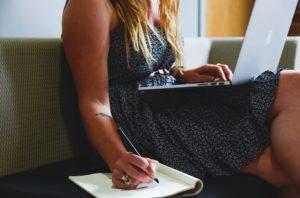 Une femme assis sur un canapé regarde son ordinateur sur ses genaoux tout en écrivant à la main sur un carnet de note