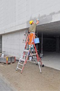 Un opérateur travaille en hauteur sur un mur extérieur