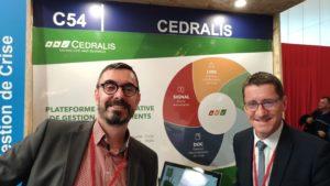 deux hommes devant le poster de la société Cedralis durant APS 2019