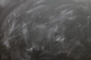 Tableau d'école noir effacé, où l'on voit encore les traces de craie.