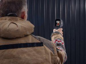 Une personne cible une zone avec la caméra de Flir détecter un point chaud.