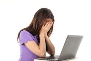Une jeune femme devant son ordinateur, montre des signes d'épuisement.