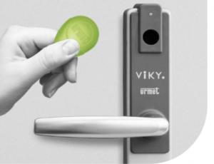 Une main avance un badge devant le lecteur Viky.