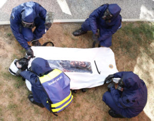 Des secouristes manipulent un sac d'extraction Ouvry dans laquelle se trouve une victime contaminée.