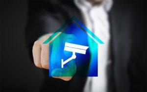 Un doigt pointe un logo de caméra sur une maison.
