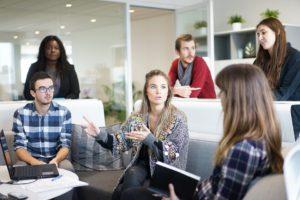 Des femmes et des hommes discutent dans un bureau.