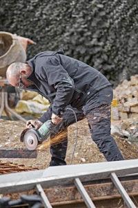 Un artisan porte le pantalon Universal Flex sur le chantier.