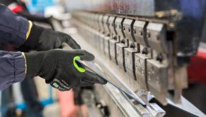 Un employé porte les gants Coreshield pour réaliser une opération industrielle.