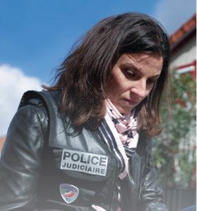Une femme commissaire de police prend des notes, de façon concentrée.