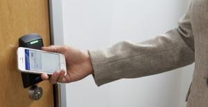 Une main munie d'un smartphone ouvre une porte en le posant devant un lecteur.