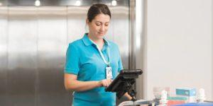 Une opératrice de nettoyage en entreprise consulte une tablette numérique durcie.