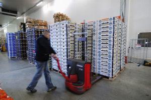 Un opérateur déplace un stock de marchandise dans un entrepôt de logistique.