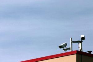 Deux caméras de vidéosurveillance sont perchées sur un toit.