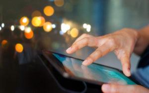 Une pêrsonnes fait glisser son doigt sur une tablette digitale.
