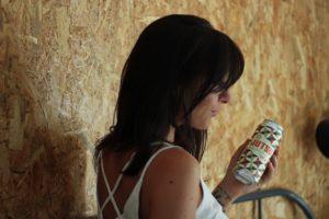 Une jeune femme tient une canette de bière.