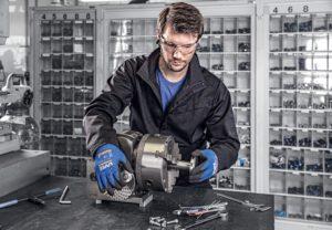 Un opérateur arborant les gants Uvex Athletic Lite se livre à un travail de précision : le montage de petites pièces.