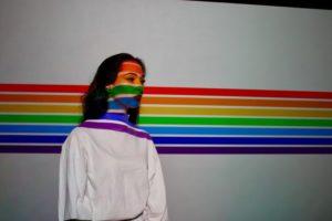 Une femme se tient devant un spectre aux couleurs LGBT.