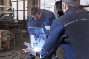 Deux artisans arborant les tenues Dynamic Flame Extreme se livrent à une opération de soudure.