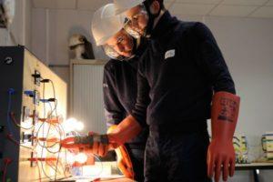Formation à l'habilitation électrique, avec port d'équipements de protection individuelle adaptés : gants en matériaux isolants, casque de protection, outil isolant