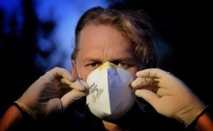 Un homme enfile un masque de protection.