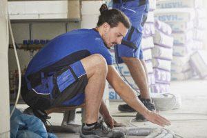 Un opérateur est penché genoux pliés pour réaliser une tâche