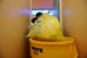 Élimination d'un sac poubelle de déchets d'activités de soins à risque infectieux (DASRI) dans un hôpital.