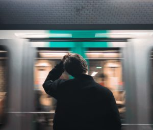 Un parisien se tient devant l'arrivée d'un train.