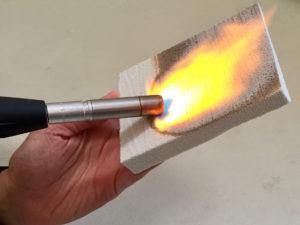 Une main porte un chalumeau sur un panneau incombustible